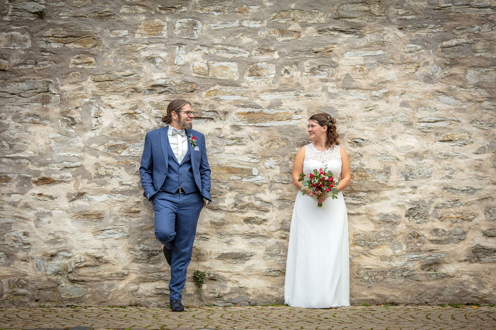 Brautpaar vor historischer Mauer